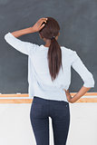 Black woman thinking in front of a blackboard