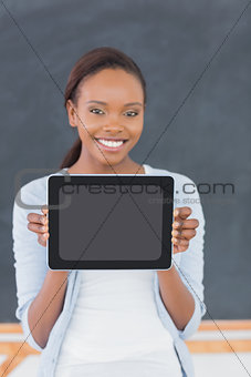 Smiling black woman holding a tablet computer