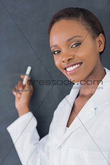 Close up of a teacher smiling while holding a chalk