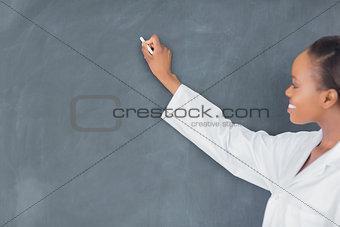 Black teacher writing on a blackboard