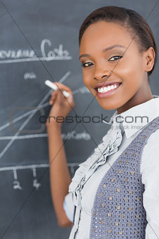 Teacher smiling while using a chalk