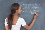 Black student writing on a blackboard