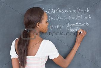 Black student writing on a blackboard