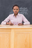 Serious teacher sitting at a desk