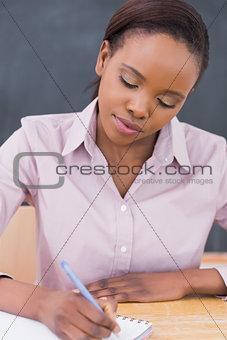 Black teacher writing on a notebook