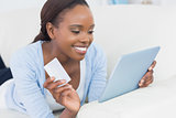 Black woman lying on front holding a credit card