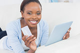 Black woman holding a tablet computer and a credit card