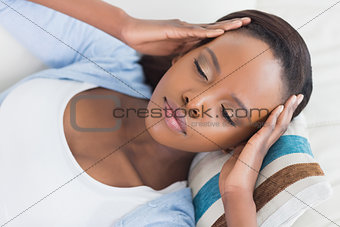 Black woman lying while having hands on temples