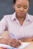 Focus on a black teacher writing on a notebook