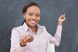 Black teacher smiling while showing the blackboard