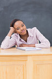 Black woman leaning on desk while looking at camera