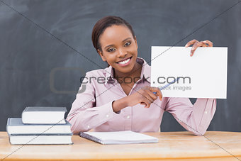 Black teacher holding a blank paper while showing it