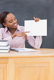 Black teacher holding a blank paper at desk