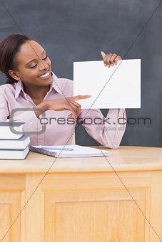 Black teacher holding a blank paper at desk