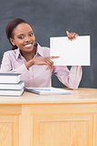 Black teacher holding a blank paper while sitting at desk