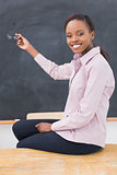 Teacher sitting on desk showing the blackboard