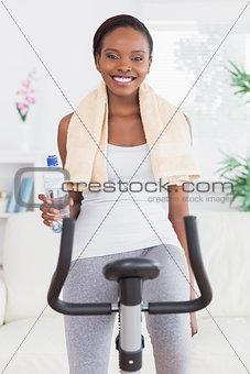Black woman on bike holding a water bottle