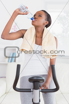 Black woman on an exercise bike drinking