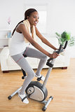 Black woman doing exercise bike while smiling