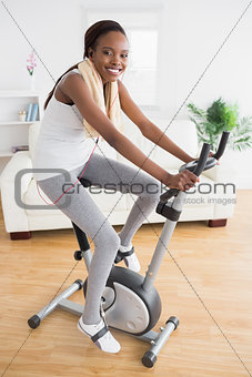 Black woman doing exercise bike with headphones