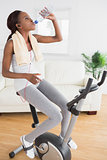 Black woman doing exercise bike while drinking