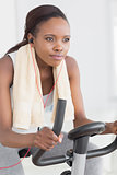 Concentrated black woman doing exercise bike
