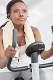 Concentrated woman doing exercise bike while listening music