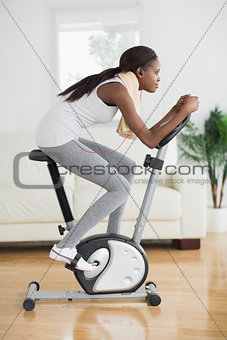 Side view of a concentrated black woman doing exercise bike