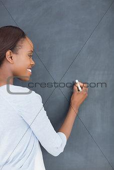 Black woman writing on a blackboard