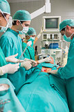 Side view of a surgical team next to a patient