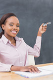 Smiling teacher showing the blackboard with her glasses
