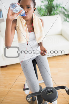 Black woman sitting on an exercise bike while drinking