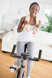 Black woman doing exercise bike while wearing a towel