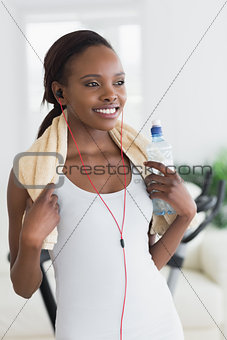 Black woman wearing a towel while holding a bottle