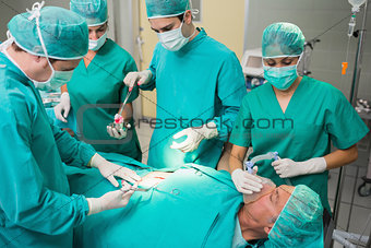 Surgeon giving surgical tool to a nurse
