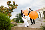 bride and groom with orange umbrellas