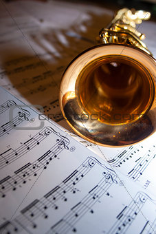 A saxophone lying on sheet music
