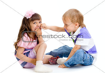 boy feeds little girl with cherry berries in studio isolated