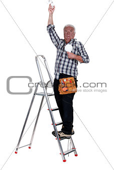 electrician on a ladder having an electric shock