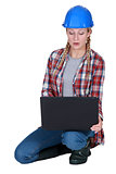 Young female builder crouching with laptop