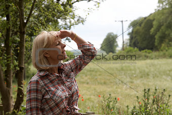 A mature woman looking over the fields