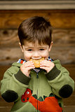 Cute little boy eating a cookie