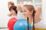 Kids and woman doing exercises with balls