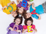 Happy school kids with colorful alphabet letters