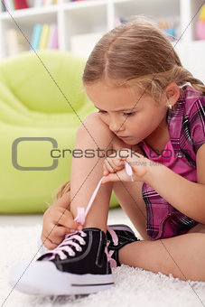 Little girl ties shoes