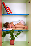 tired kid sleeping on the shelf with a book instead of a pillow