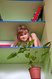  playful little girl hiding on the shelf