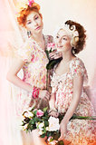 Freshness. Two Young Pretty Women in Classic Vintage Dresses with Flowers. Pin-up Style
