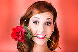 Woman gripping red rose between her teeth