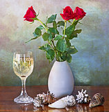 red roses in vase, white wine glass and shells